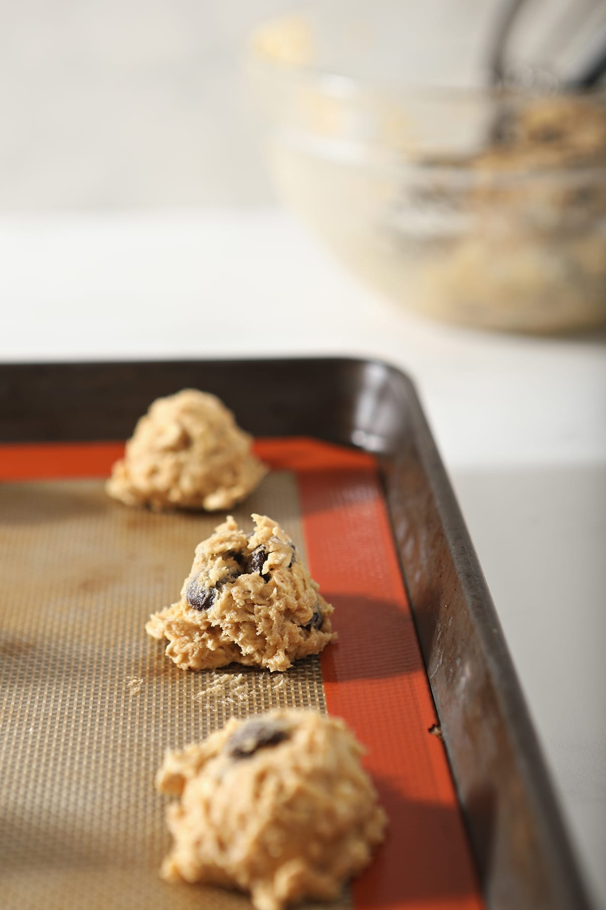 One tablespoon cookies on a lined baking sheet before baking