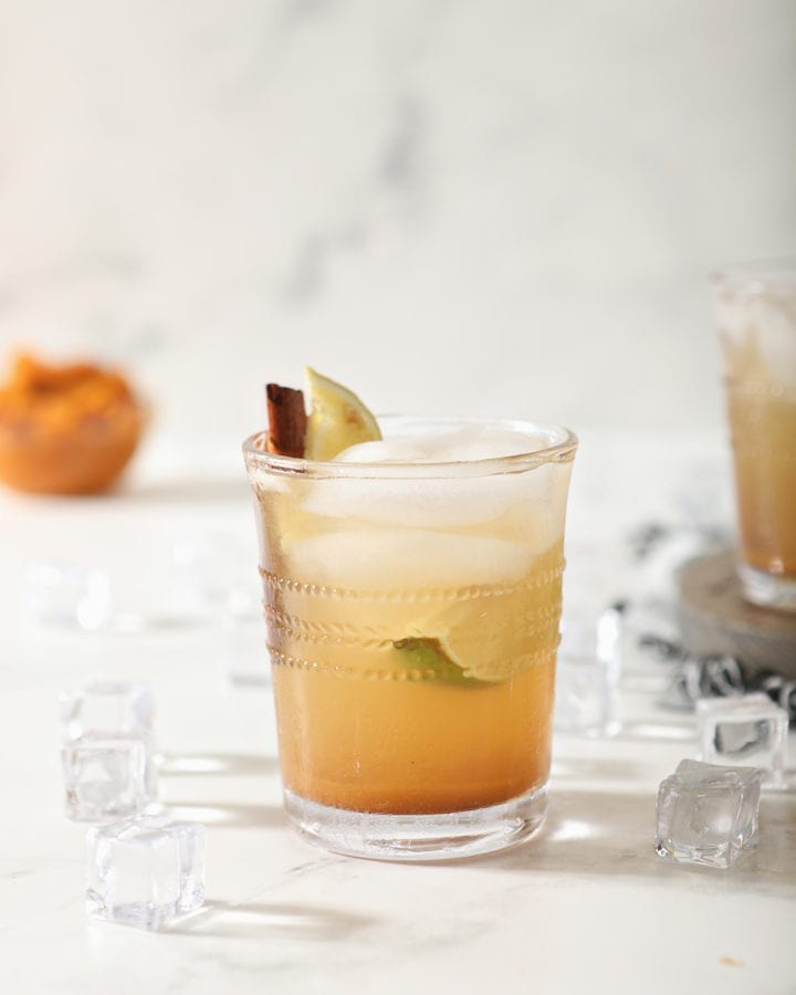A singular glass of Pumpkin Spice Mule on marble with a bowl of pumpkin puree behind it