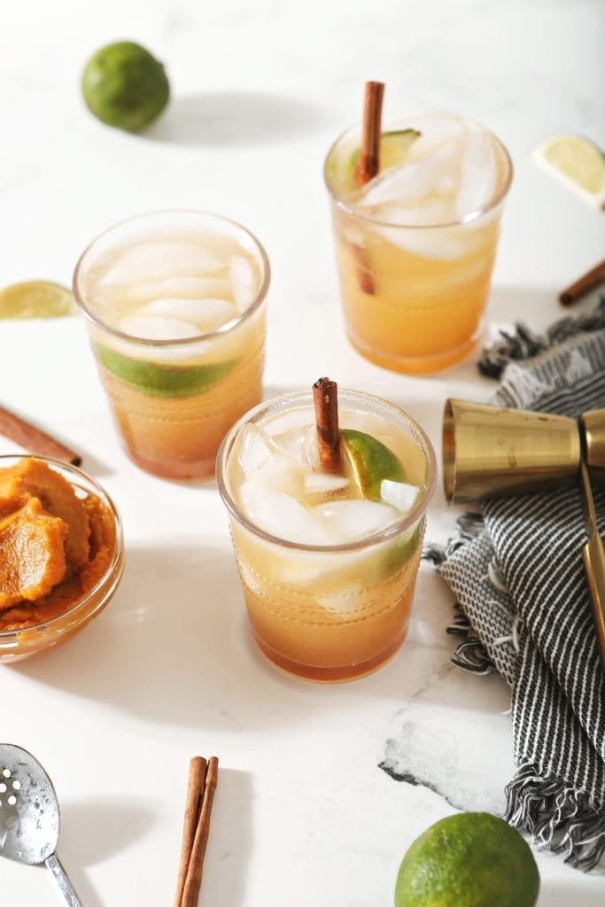 Three Pumpkin Mules, garnished with cinnamon sticks and lime wedges, surrounded by limes, pumpkin and a jigger on marble