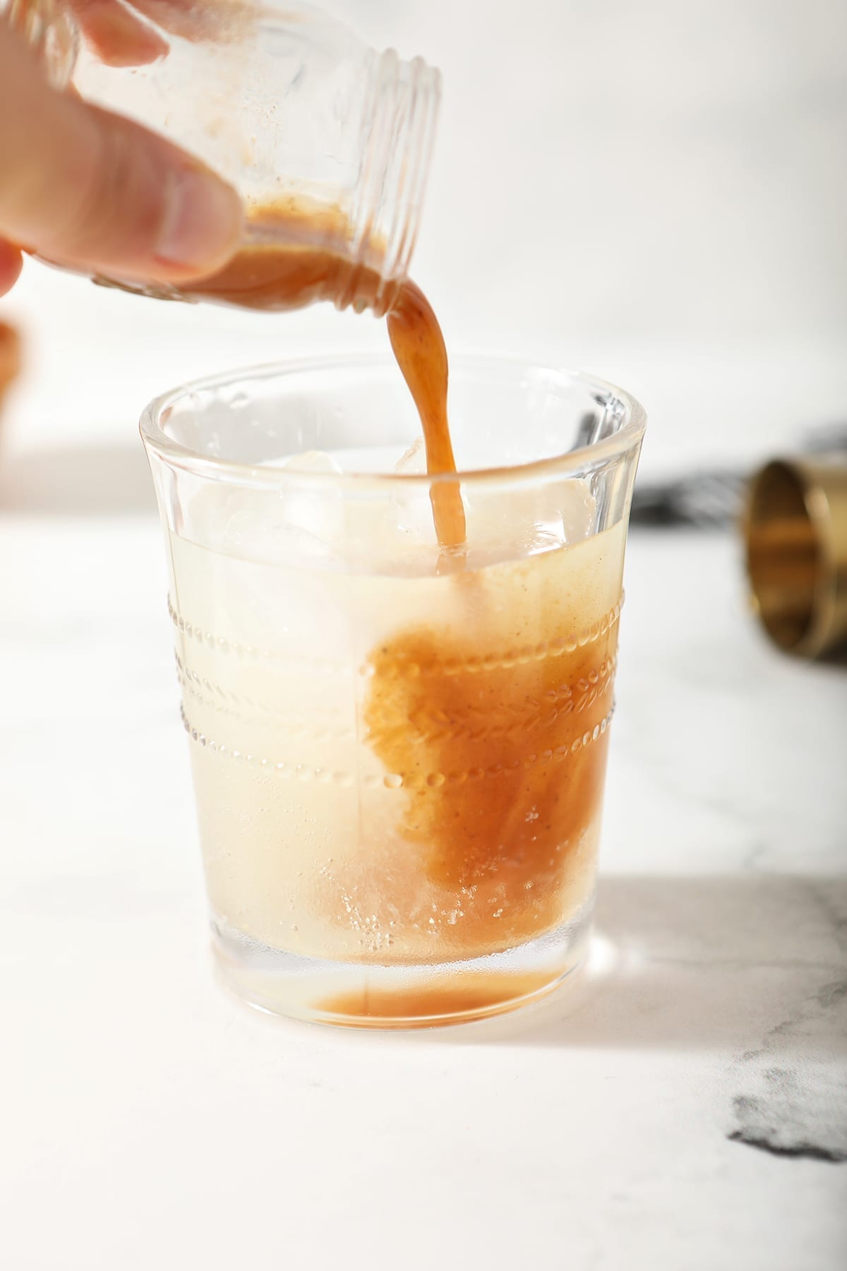 A shot of pumpkin spice syrup is poured into the drink