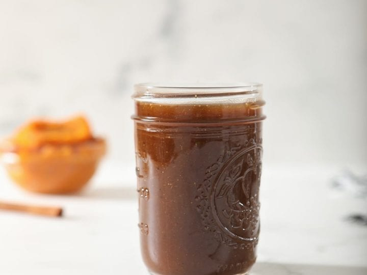 A jar of Homemade Pumpkin Spice Syrup on marble with a bowl of pumpkin puree and a stick of cinnamon behind it