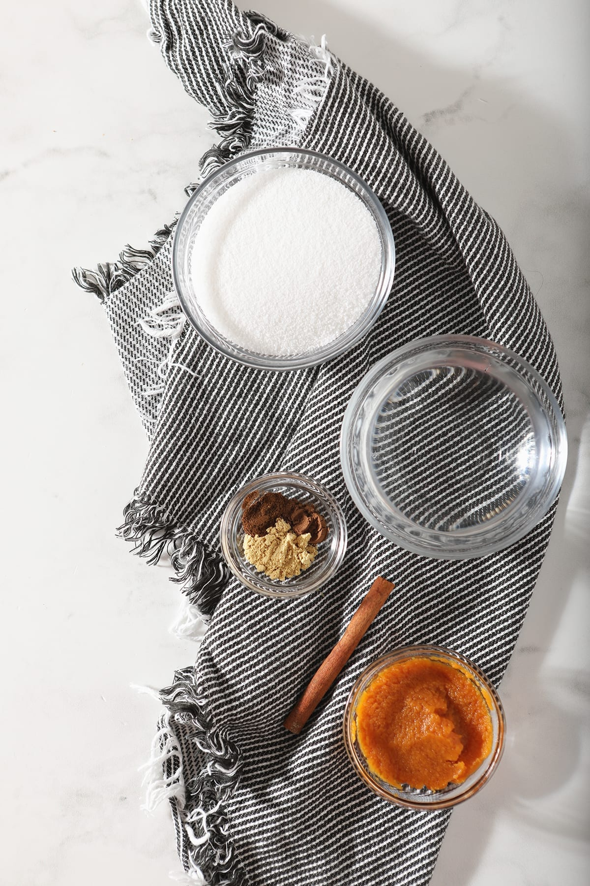 Granulated sugar, water, pumpkin pure and spices sit on a gray striped towel on marble