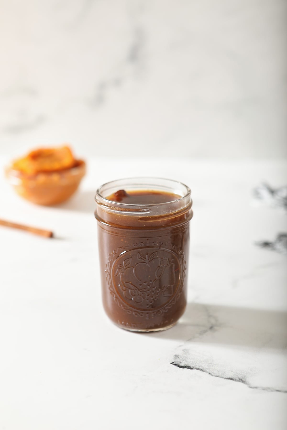 A jar of Pumpkin Spice Syrup sits on marble with a cinnamon stick and pumpkin puree behind it