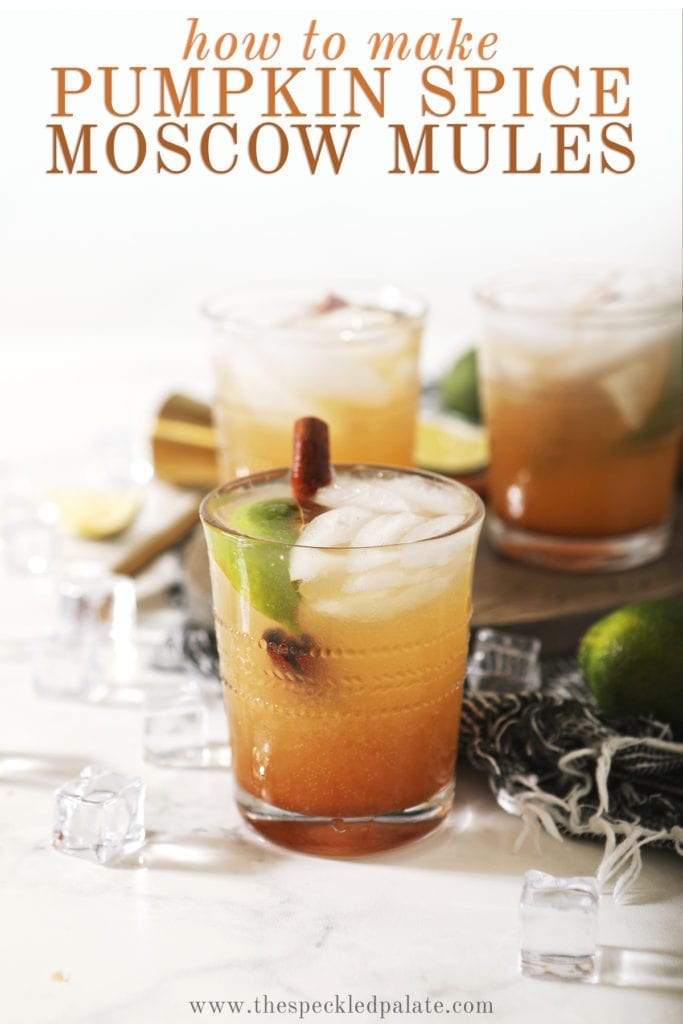 Three glasses holding Pumpkin Spice Mule on gray cloth and a wooden board with the words 'how to make pumpkin spice moscow mules'