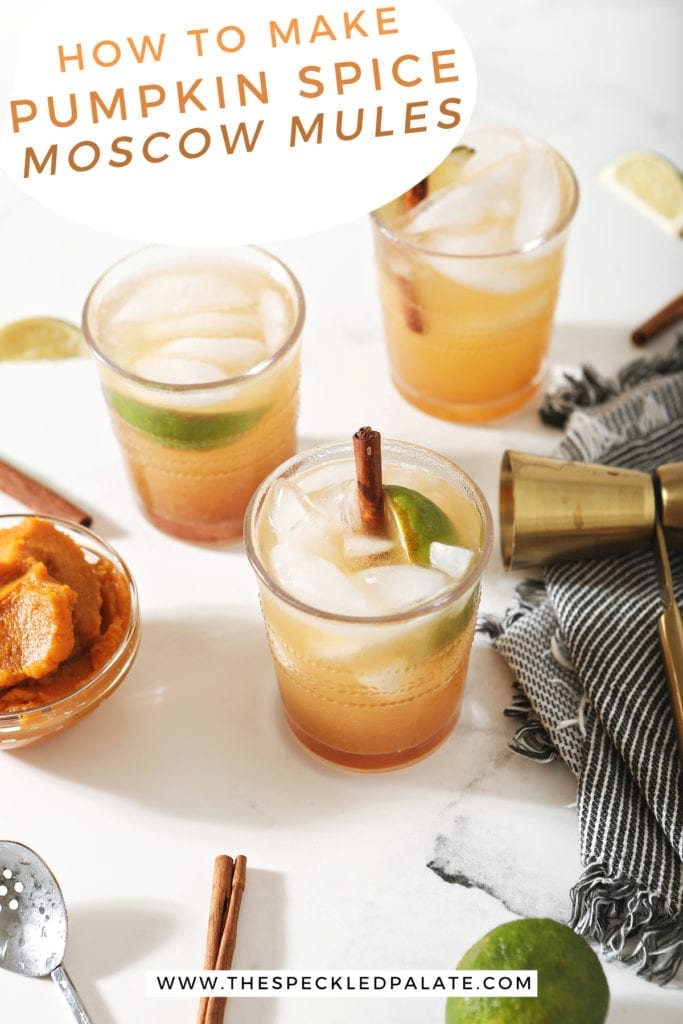 Three Pumpkin Mules, garnished with cinnamon sticks and lime wedges, surrounded by limes, pumpkin and a jigger on marble with the text 'how to make pumpkin spice moscow mules'