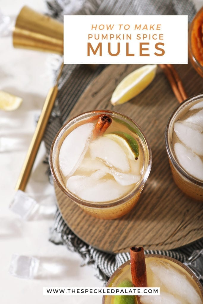 Overhead of three Pumpkin Spice Moscow Mules on a wooden serving dish next to to limes, a jigger and a bowl of pumpkin puree with the text 'how to make pumpkin spice mules'