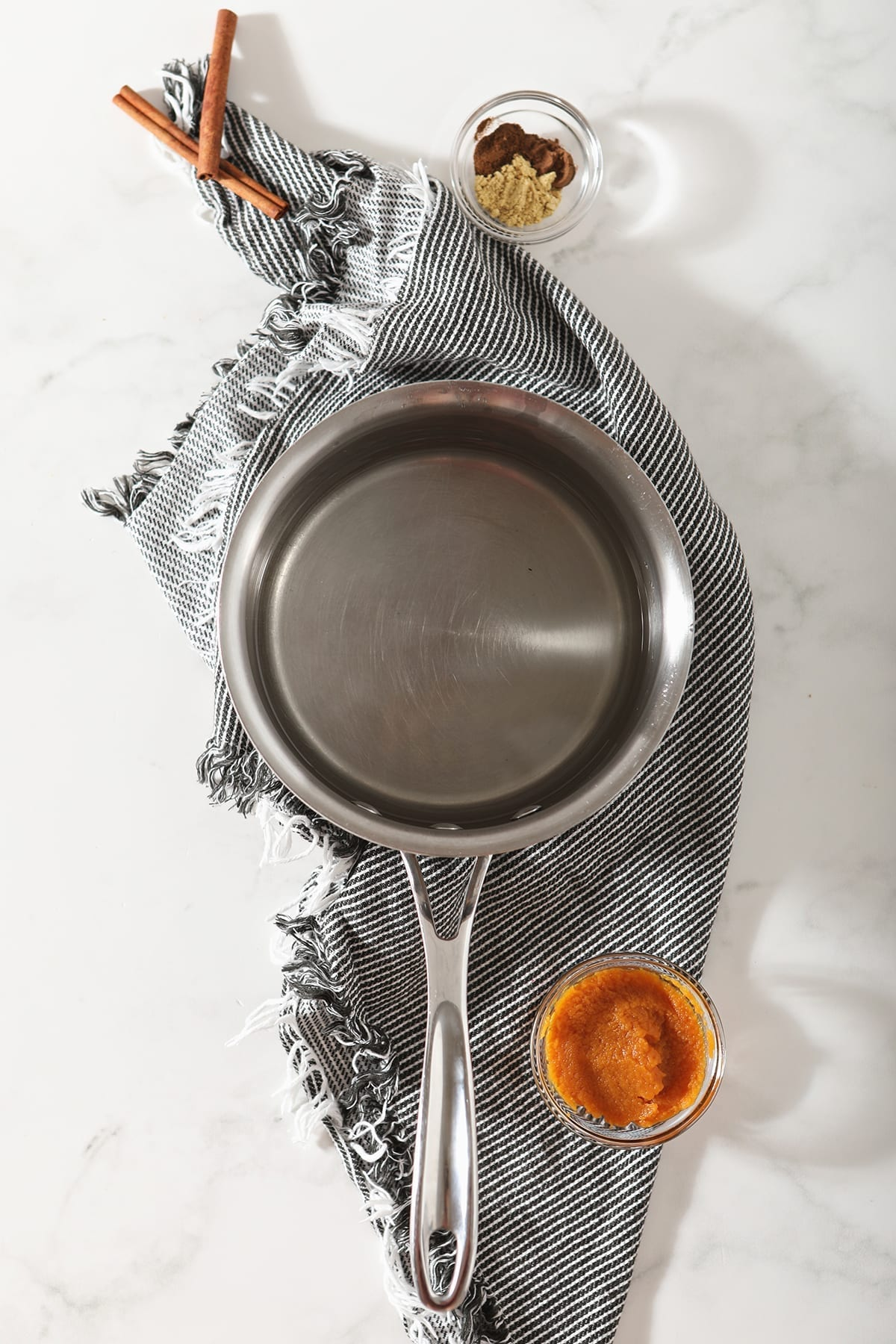 Water and sugar in a saucepan with other ingredients for the pumpkin simple syrup on marble
