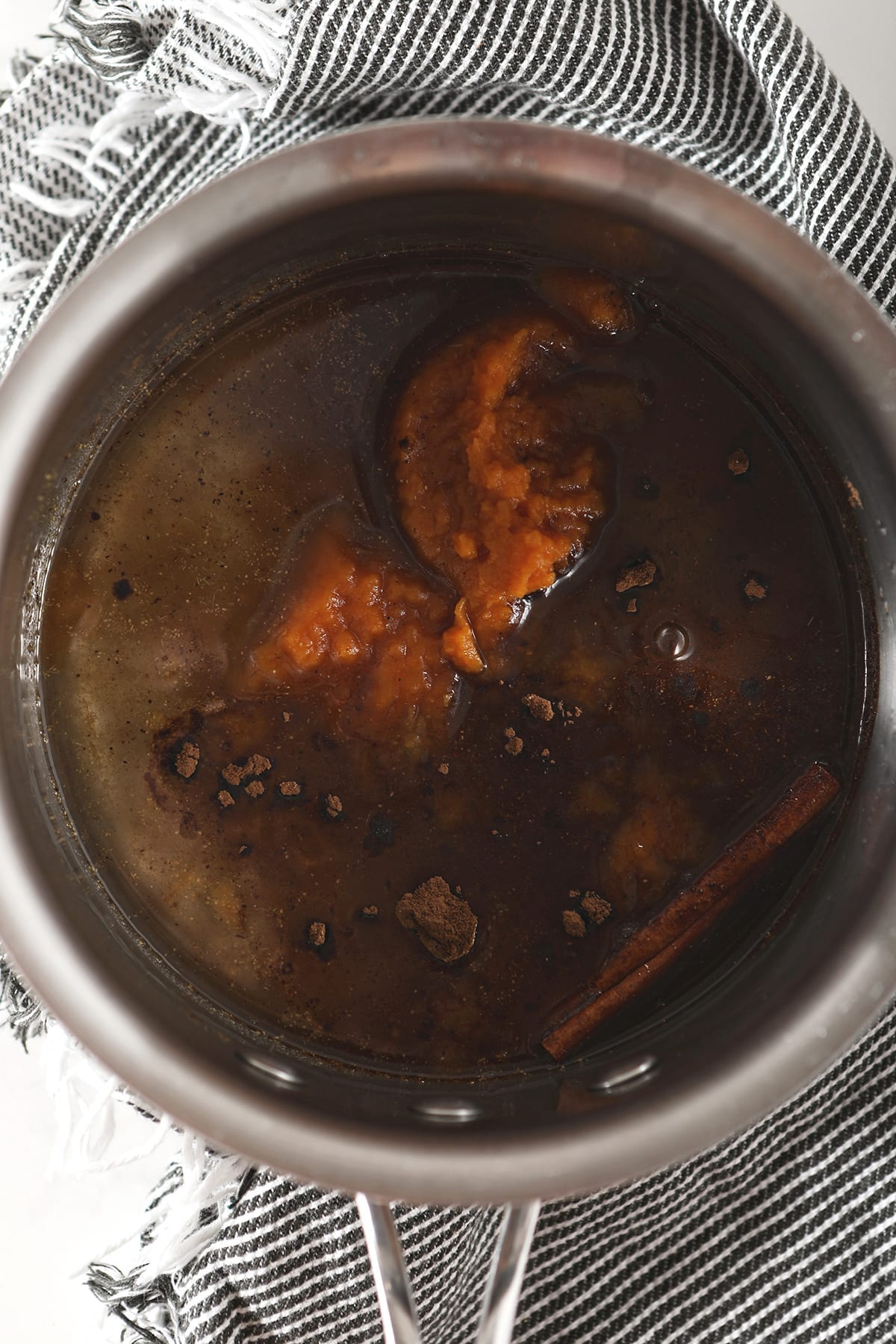Pumpkin, spices and other ingredients steep in simple syrup in a saucepan