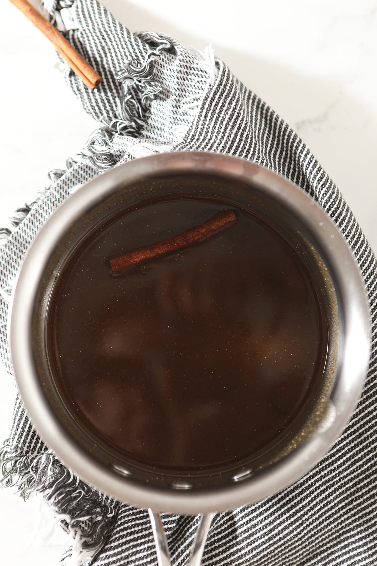 Pumpkin Spice Syrup steeps in a saucepan on marble