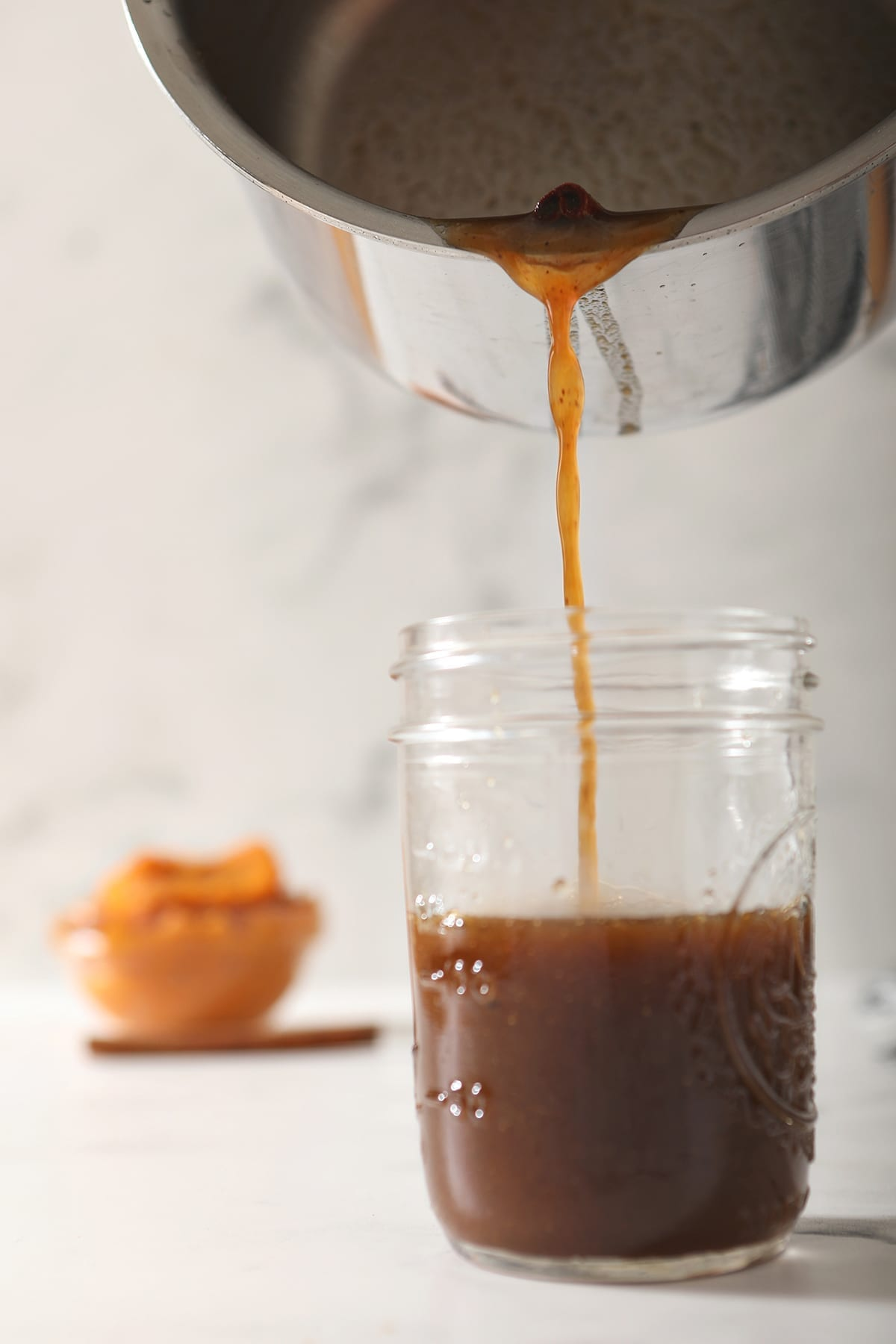 Pumpkin Spice Syrup pours into a mason jar from a saucepan