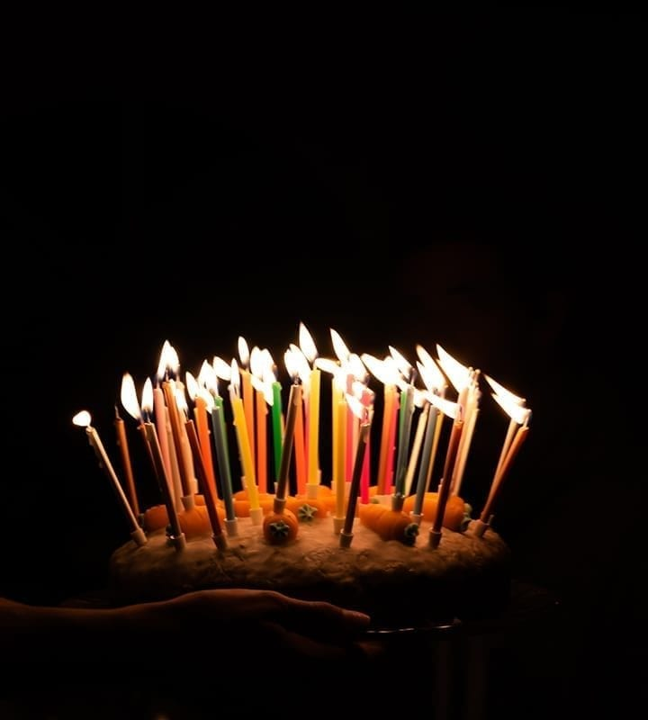 A person holds a birthday cake with lit candles in darkness