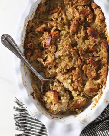 A spoon holding stuffing sits in a casserole dish holding the final baked dish