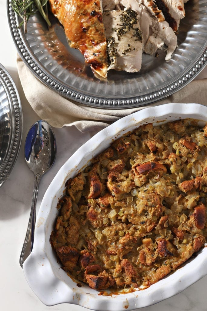 Brioche Bread stuffing in a casserole dish on the holiday table next to sliced turkey