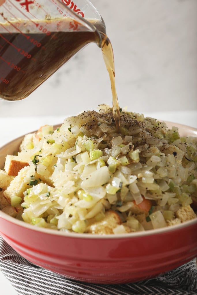 Vegetable stock pours on top of sauteed vegetables, spices and cubed bread to make the bread stuffing recipe