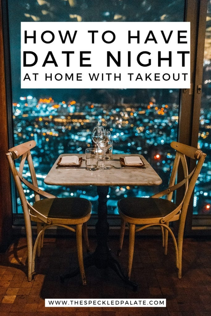 A table for two set next to a window with lights twinkling outside with the text 'how to have date night at home with takeout'