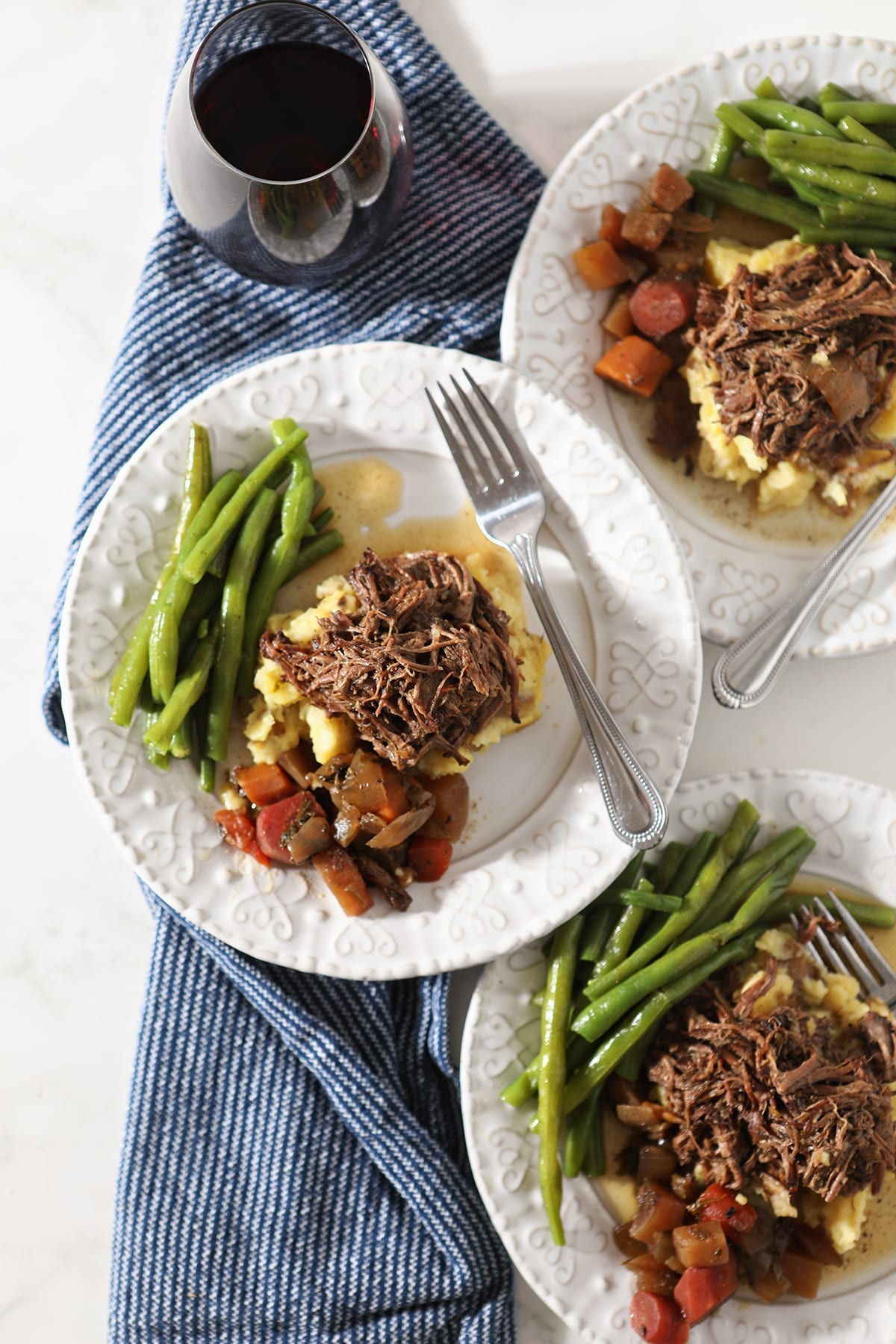 Three plates hold shredded slow cooker pot roast with mashed potatoes, steamed green beans and slow cooked veggies from above