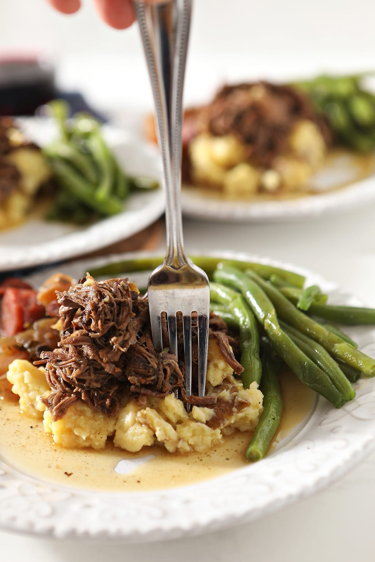 Close up of a fork sticking shredded slow cooker pot roast on top of mashed potatoes and next to steamed green beans