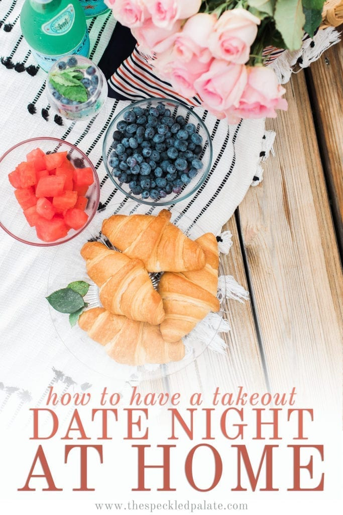 Overhead of a picnic spread with croissants, fruit and roses with the text 'how to have a takeout date night at home'
