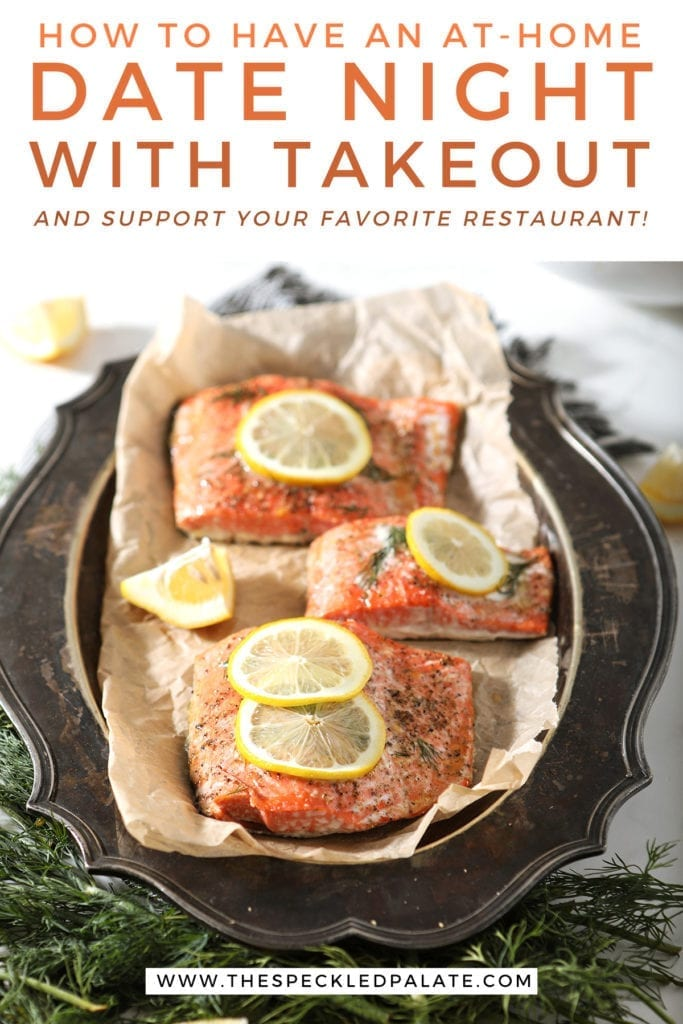 Close up of roasted salmon filets with lemon slices and thyme on them on a tarnished silver platter with the text 'how to have an at-home date night with takeout and support your favorite restaurant!'