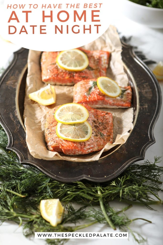 Close up of roasted salmon filets with lemon slices and thyme on them on a tarnished silver platter with the text 'how to have the best at-home date night'
