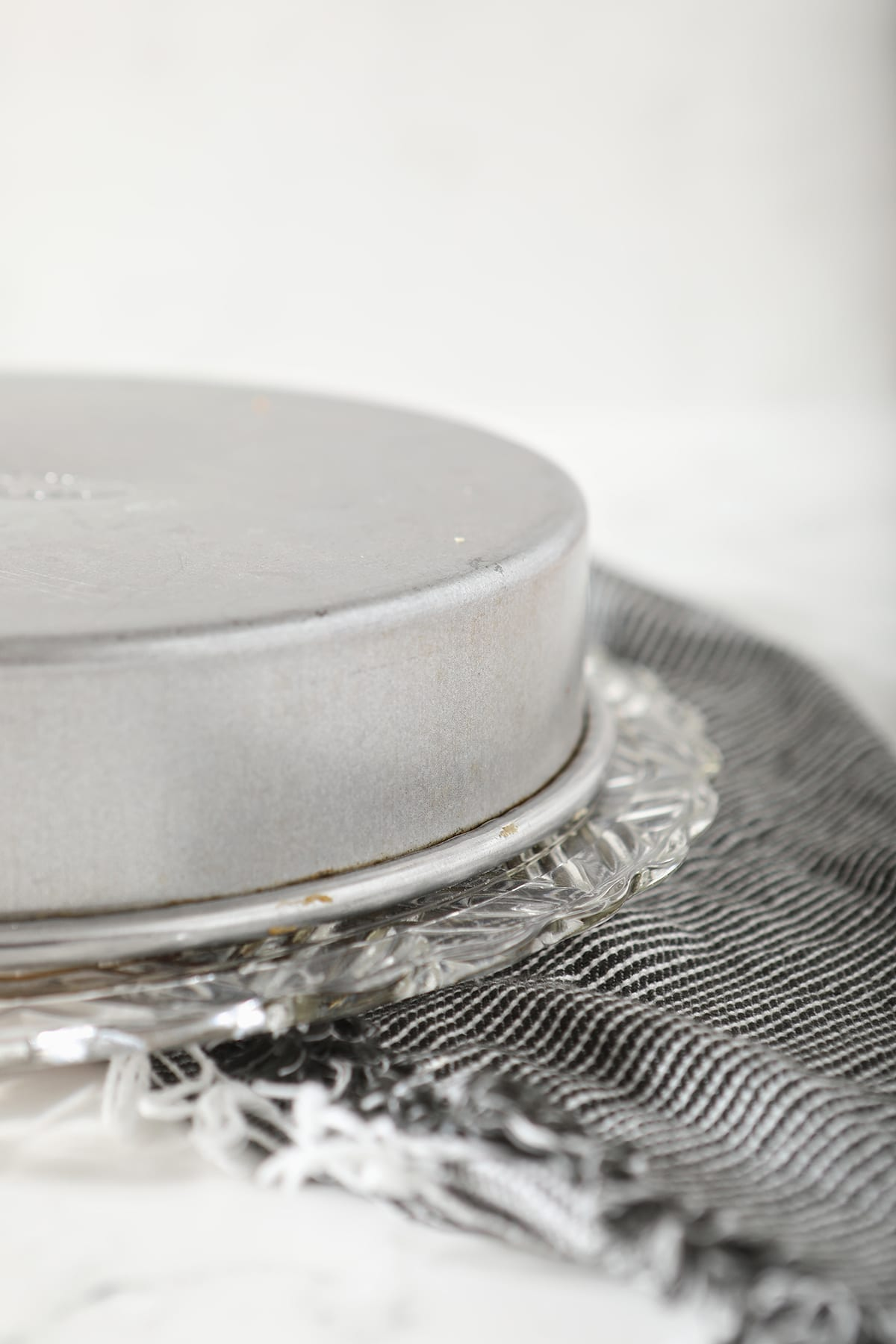 An upside down cake tin on a glass cake stand