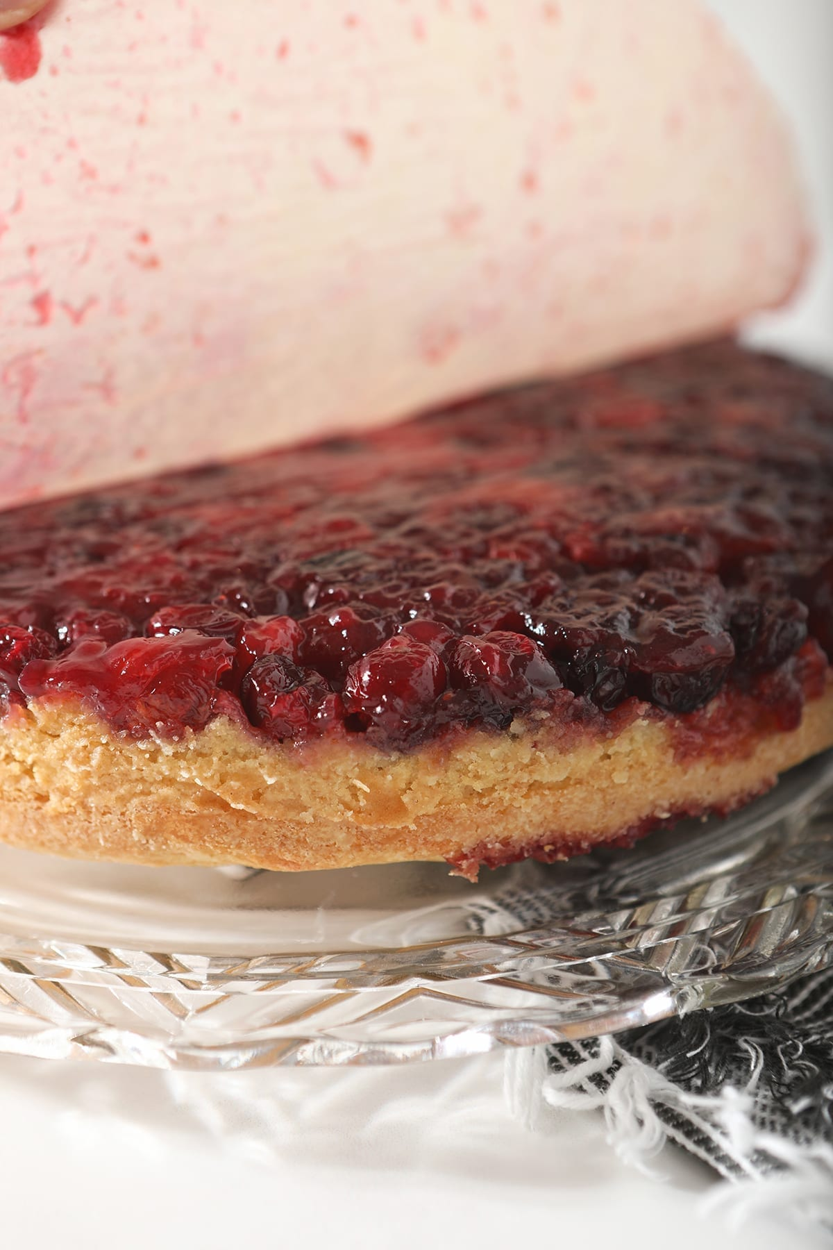 Parchment paper is peeled off of the cranberry sauce layer of the cake