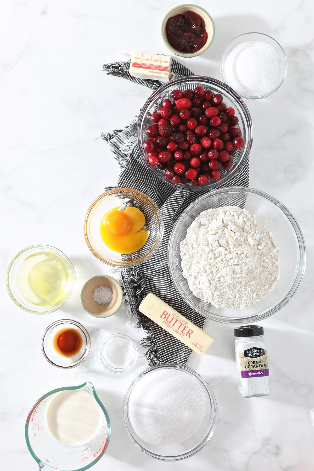 Ingredients for the Cranberry Cake, shown from above in bowls, on a gray striped towel and marble counter