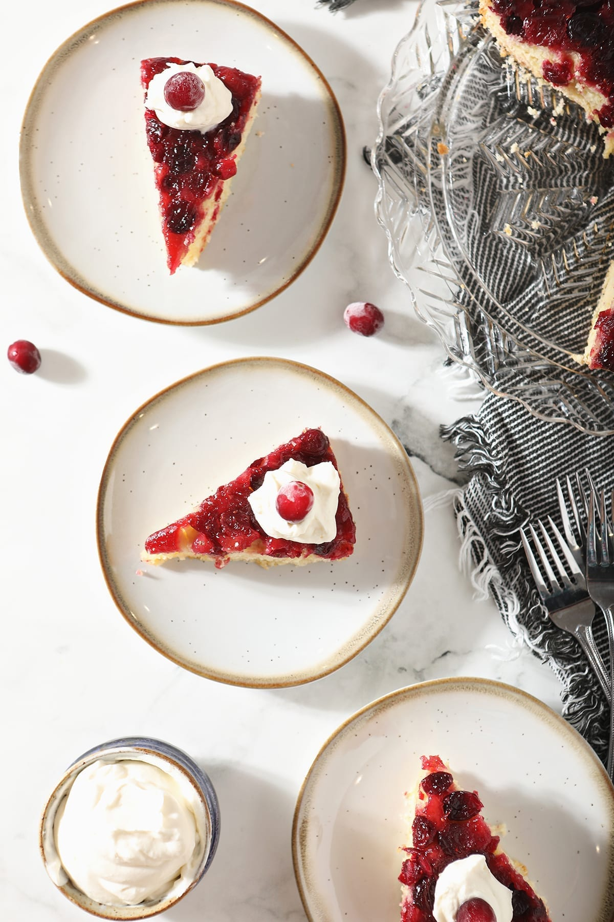 Overhead of three plates holding slices of Cranberry Cake