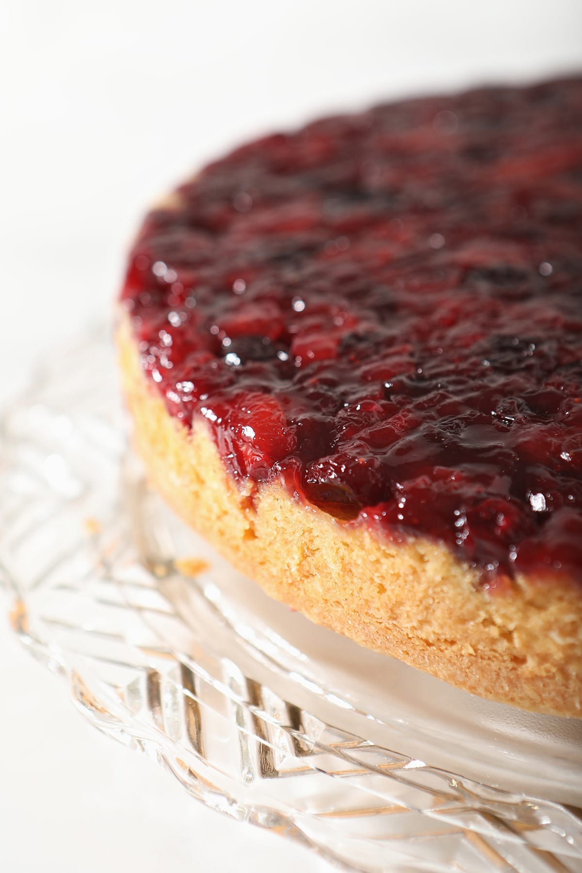 Close up of the Upside Down Cranberry Cake on a decorative glass cake plate