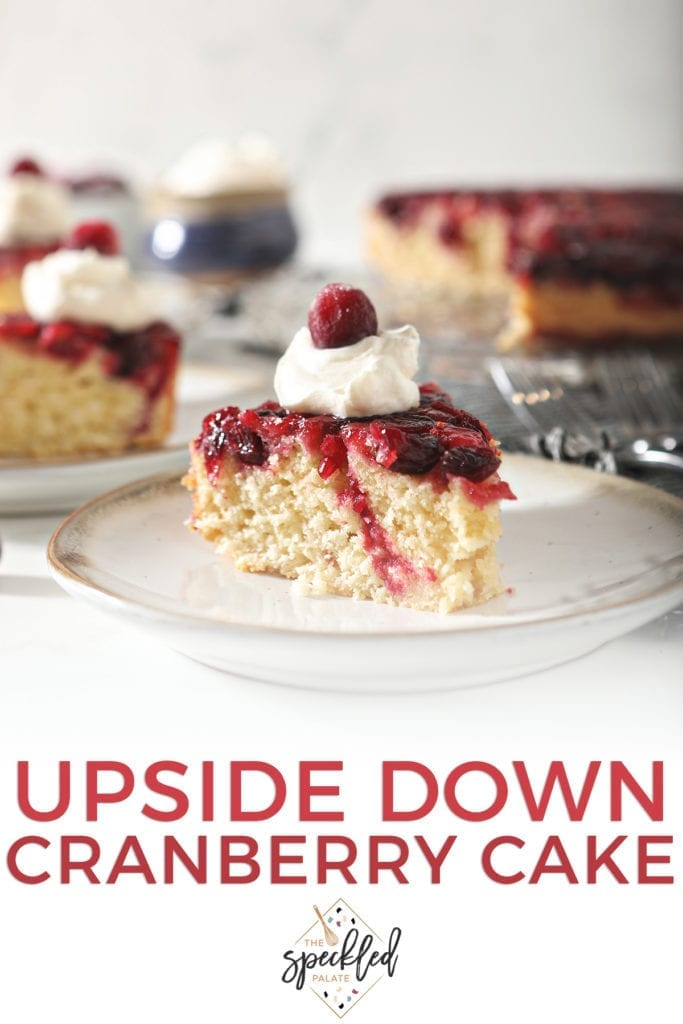 A slice of cranberry upside down cake garnished with a dollop of whipped cream and a cranberry on a white pottery plate with other slices behind it with the text 'upside down cranberry cake'