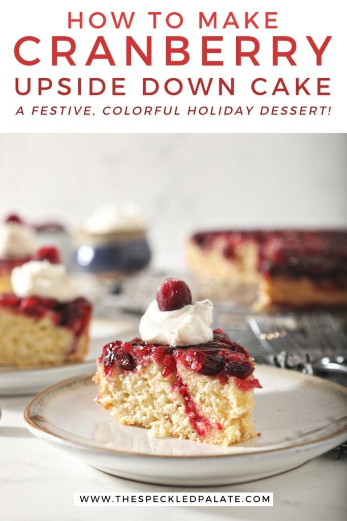 A slice of cranberry upside down cake garnished with a dollop of whipped cream and a cranberry on a white pottery plate with other slices behind it with the text 'how to make cranberry upside down cake. a festive, colorful holiday dessert!'