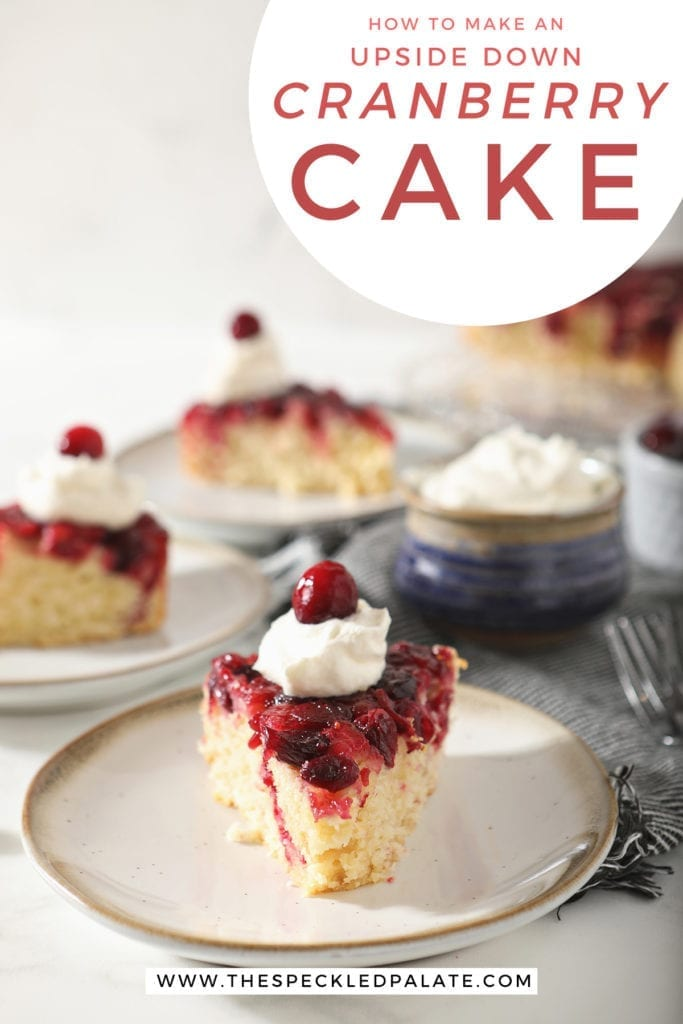 A slice of cranberry upside down cake garnished with a dollop of whipped cream and a cranberry on a white pottery plate with other slices behind it with the text 'how to make an upside down cranberry cake'