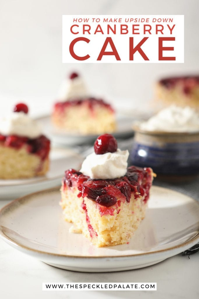A slice of cranberry upside down cake garnished with a dollop of whipped cream and a cranberry on a white pottery plate with other slices behind it with the text 'how to make upside down cranberry cake'