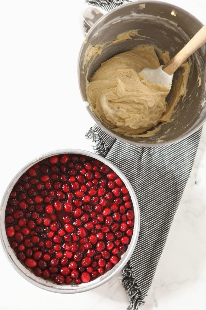 A cake pan holding the cranberries and their sauce sits next to a bowl holding cake batter