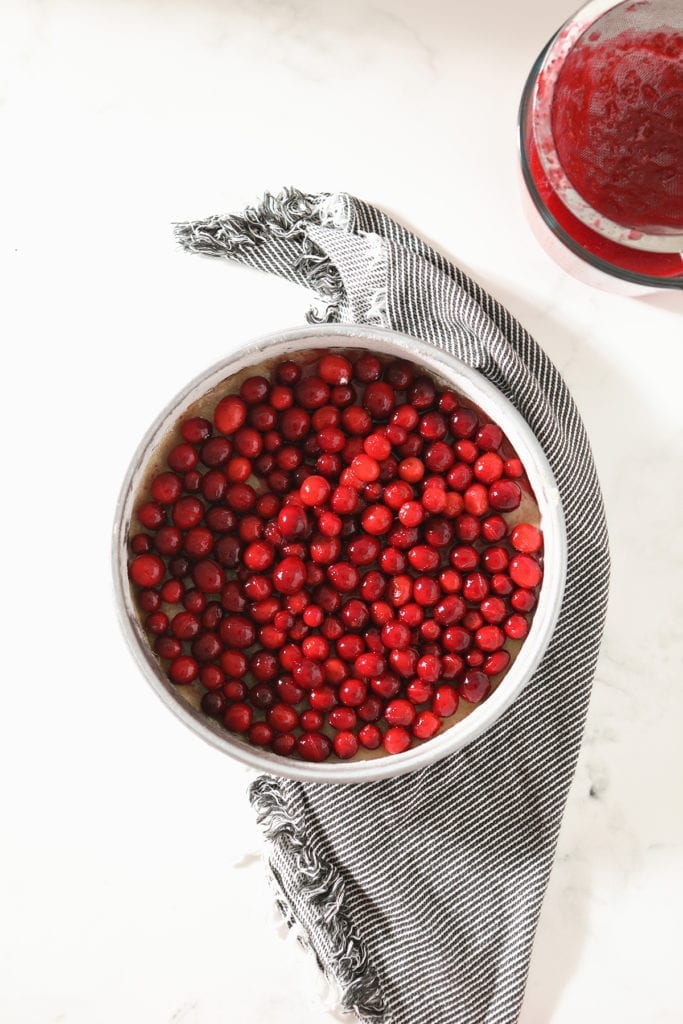 Cranberries in the bottom of a round cake pan on top of a striped gray towel