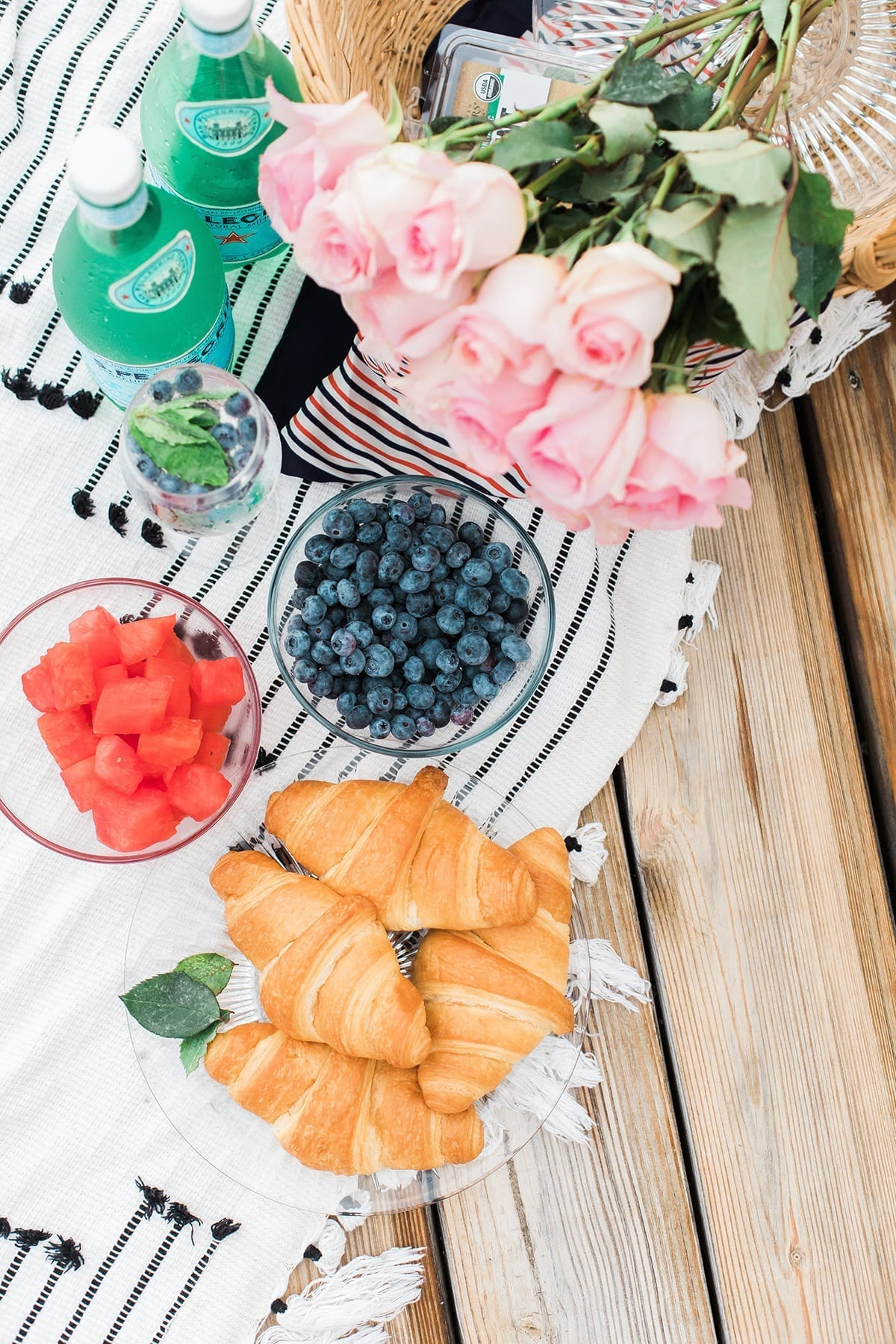 Overhead of a picnic spread with croissants, fruit and roses