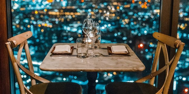 A table for two set next to a window with lights twinkling outside