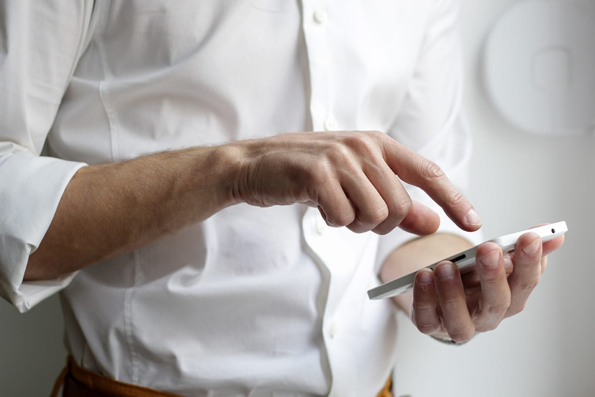 A man in a white shirt types numbers into a cell phone