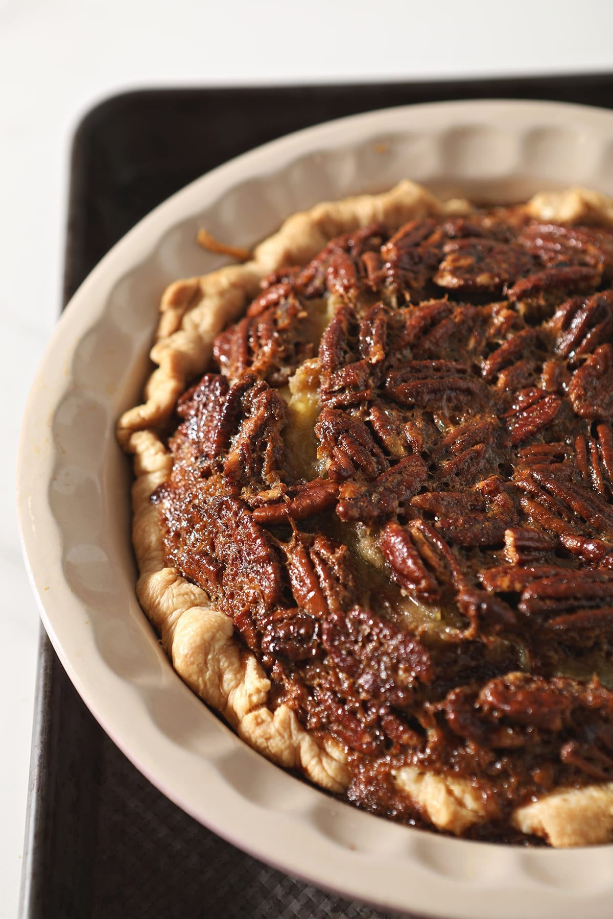 Close up of a Bourbon Pecan Pie on a baking sheet just after baking