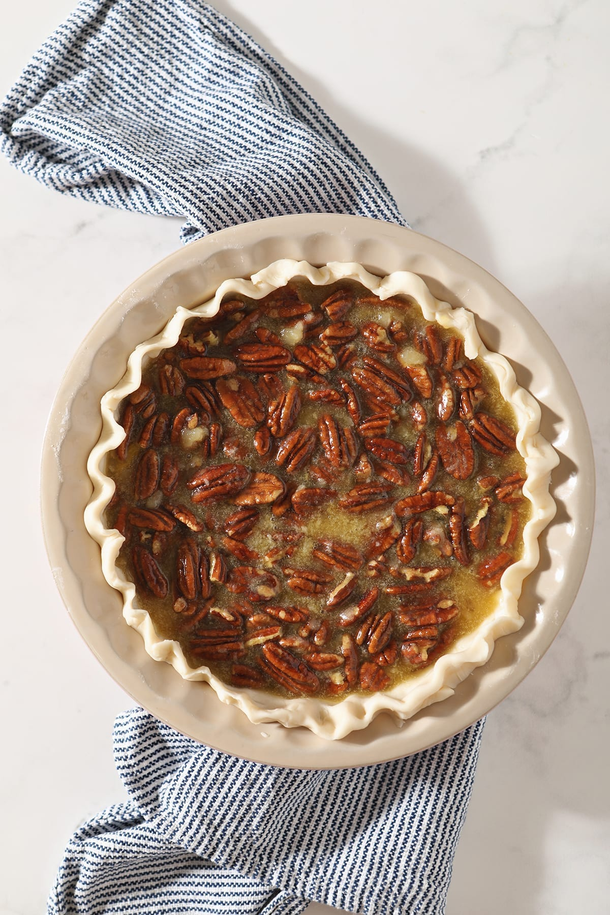 A Bourbon Pecan Pie sits on a blue and white striped towel before baking