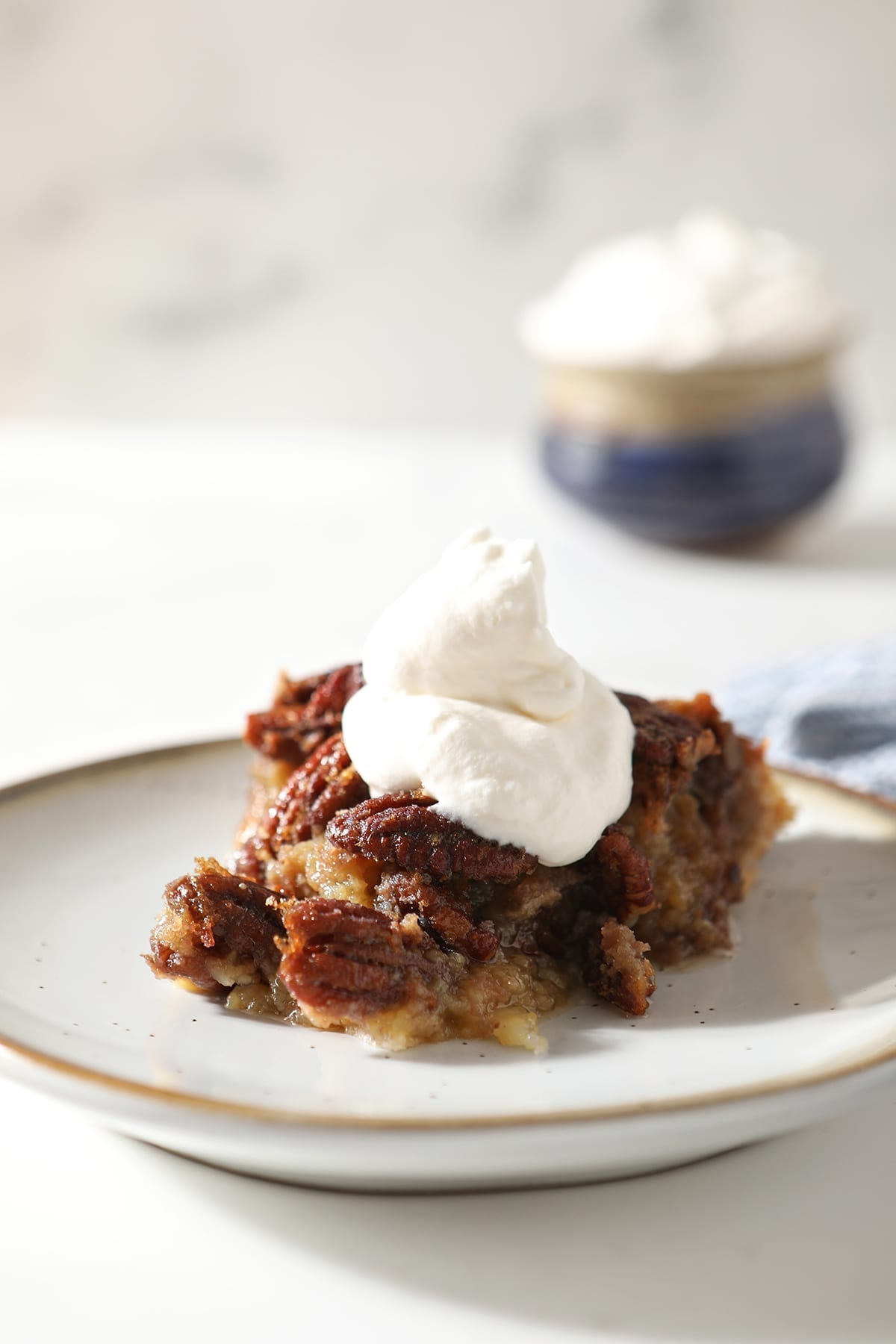 Close up of a slice of Bourbon Pecan Pie with whipped cream on top