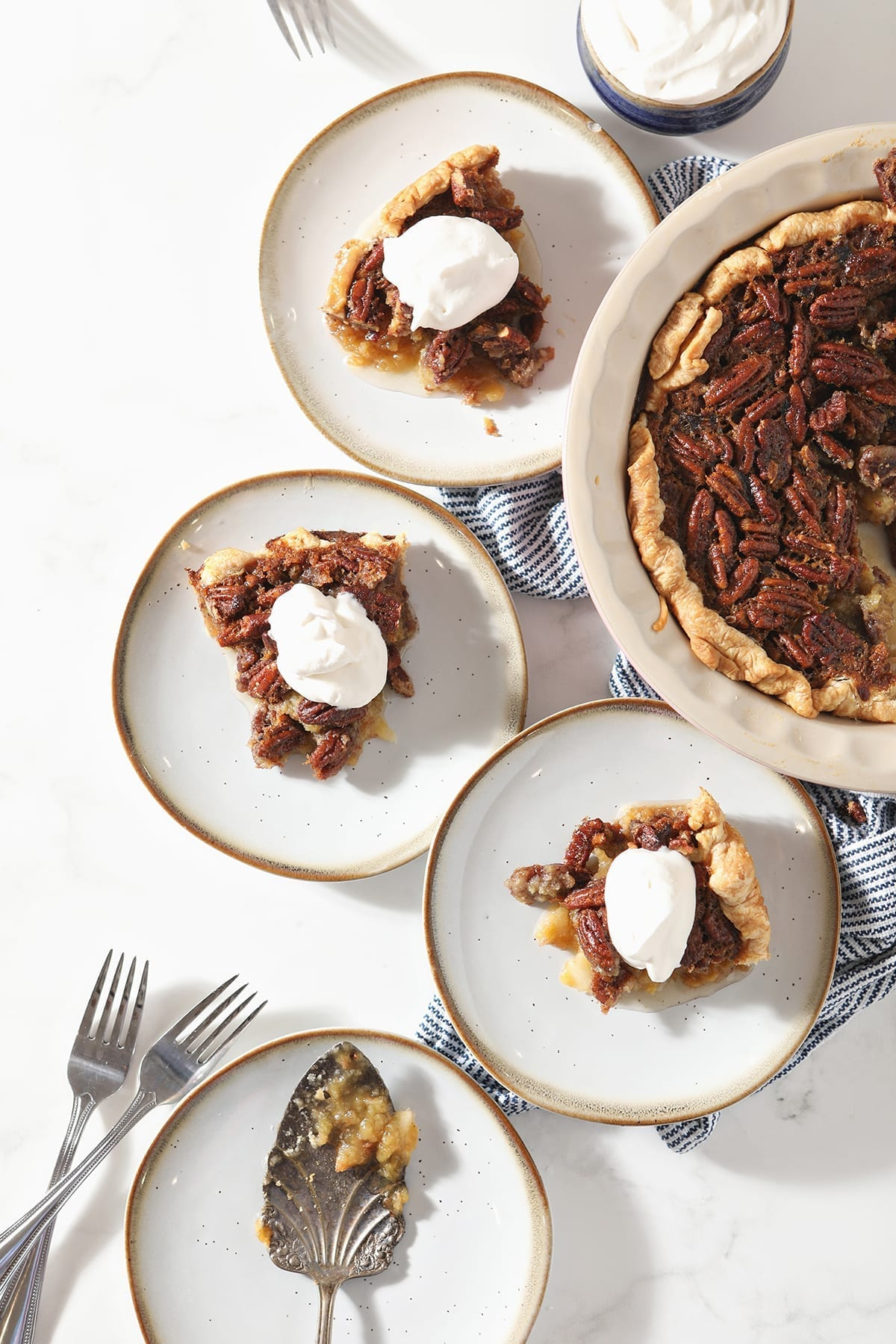 Three slices of Bourbon Pecan Pie sit on white plates next to the rest of the pie, a bowl of whipped cream and a plate holding the serving fork