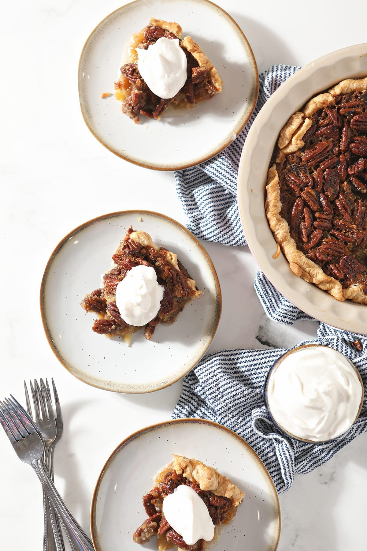 Overhead of three slices of Bourbon Pecan Pie on plates with forks next to the rest of the pie and a bowl of whipped cream