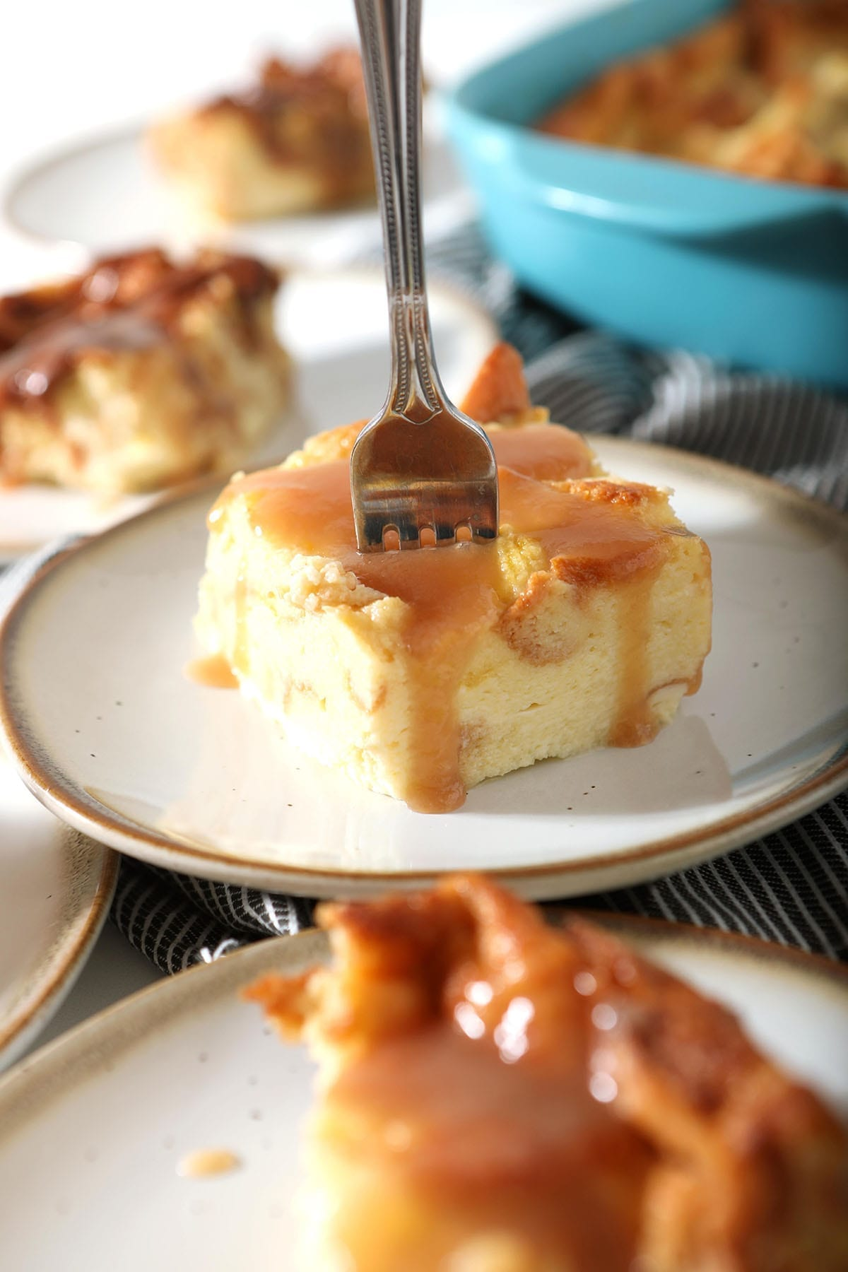 A fork spears a slice of bread pudding with caramel