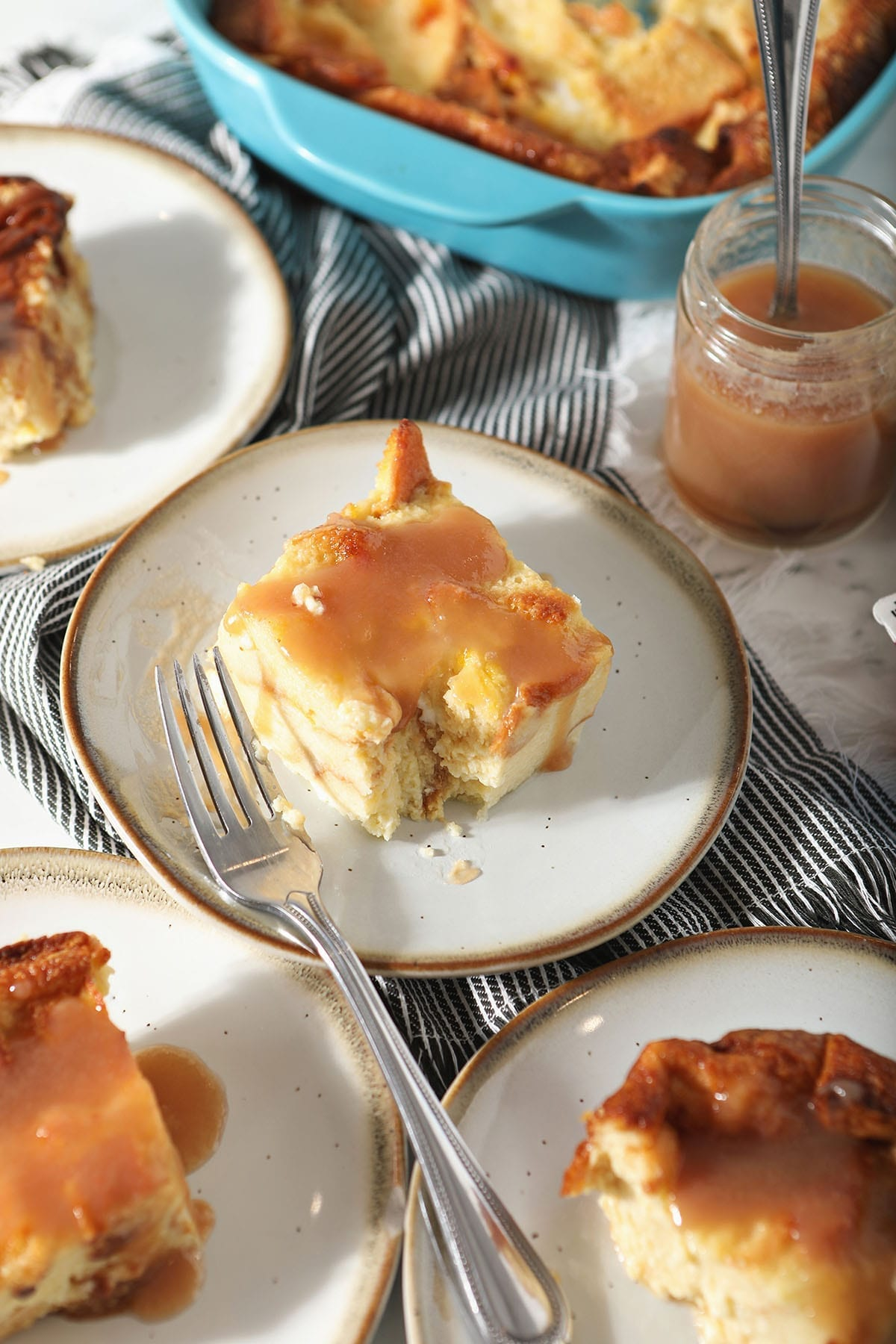 A cut into piece of bread pudding with caramel sauce on a white plate, surrounded by other slices of the dessert and a jar of caramel sauce