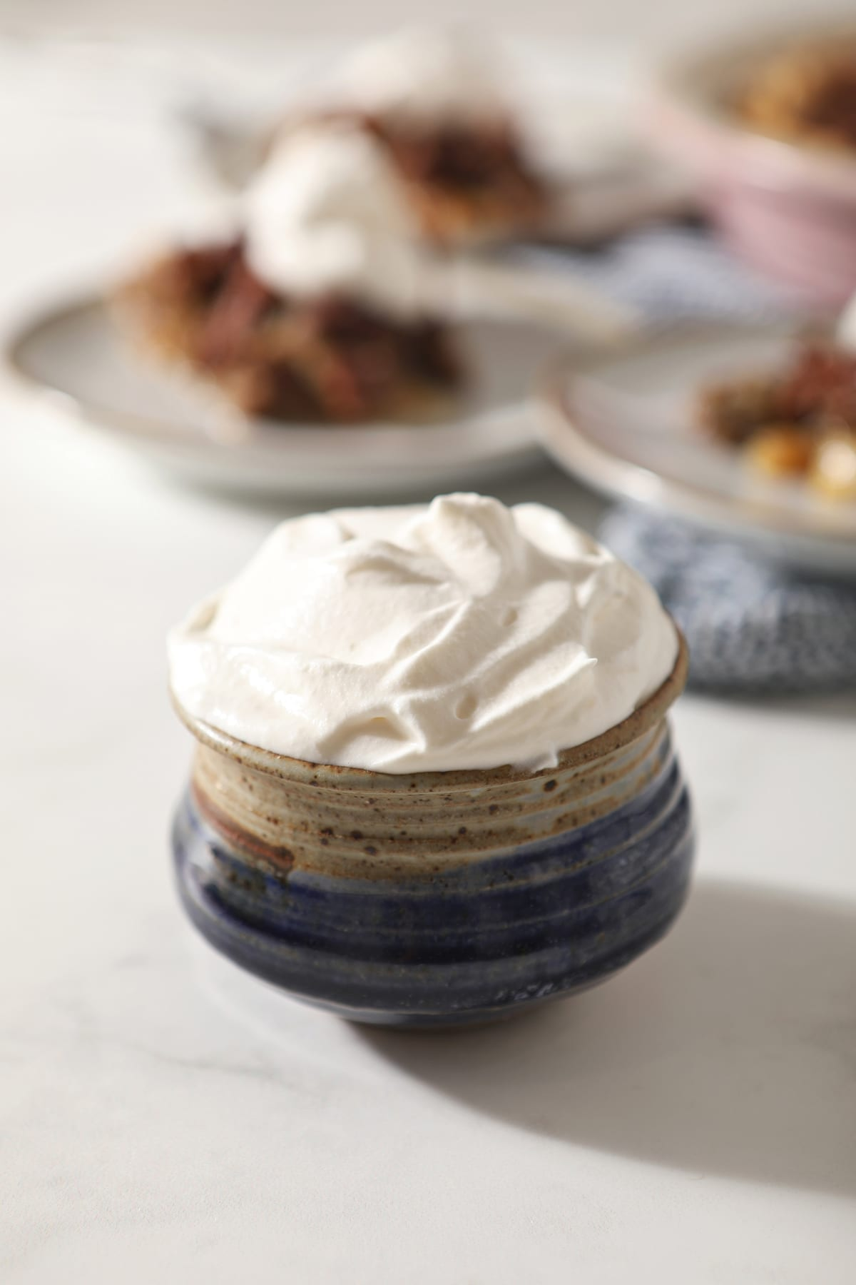Close up of a blue pottery bowl holding a serving of homemade sweetened whipped cream