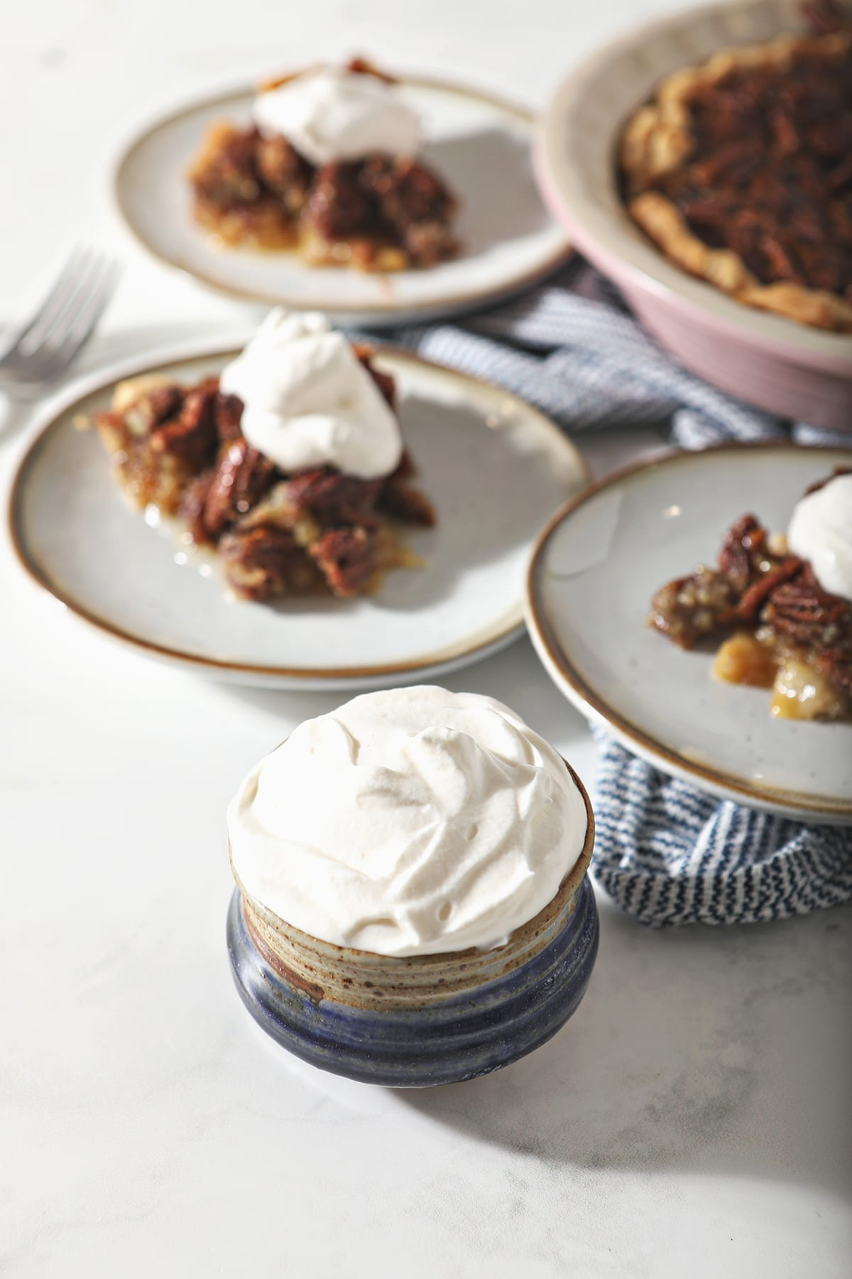 A blue pottery bowl holding a serving of homemade sweetened whipped cream next to three plates holding slices of pecan pie