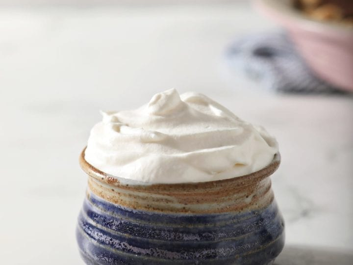 A blue pottery bowl holding a serving of homemade sweetened whipped cream in front of a pink pie plate