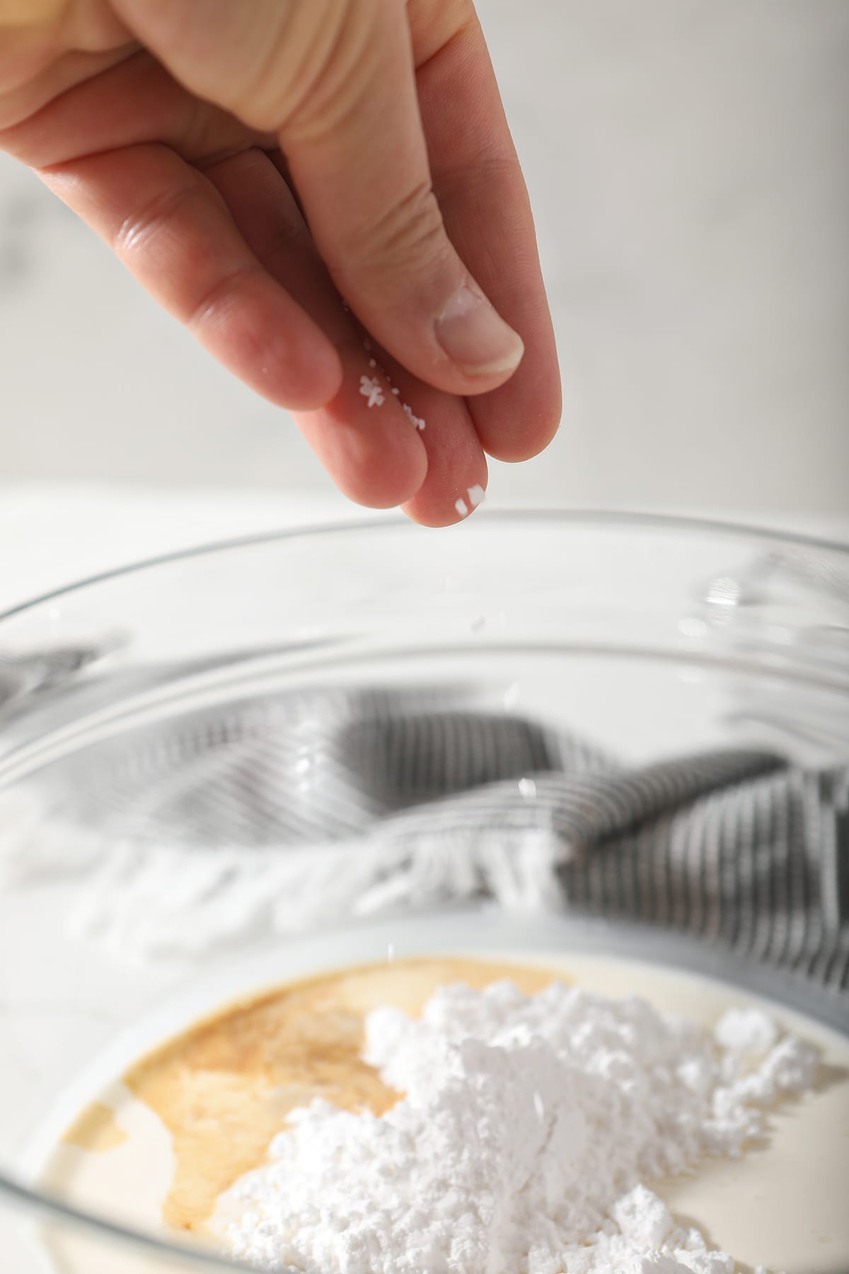 A hand sprinkles salt into a bowl holding cream, powdered sugar and vanilla