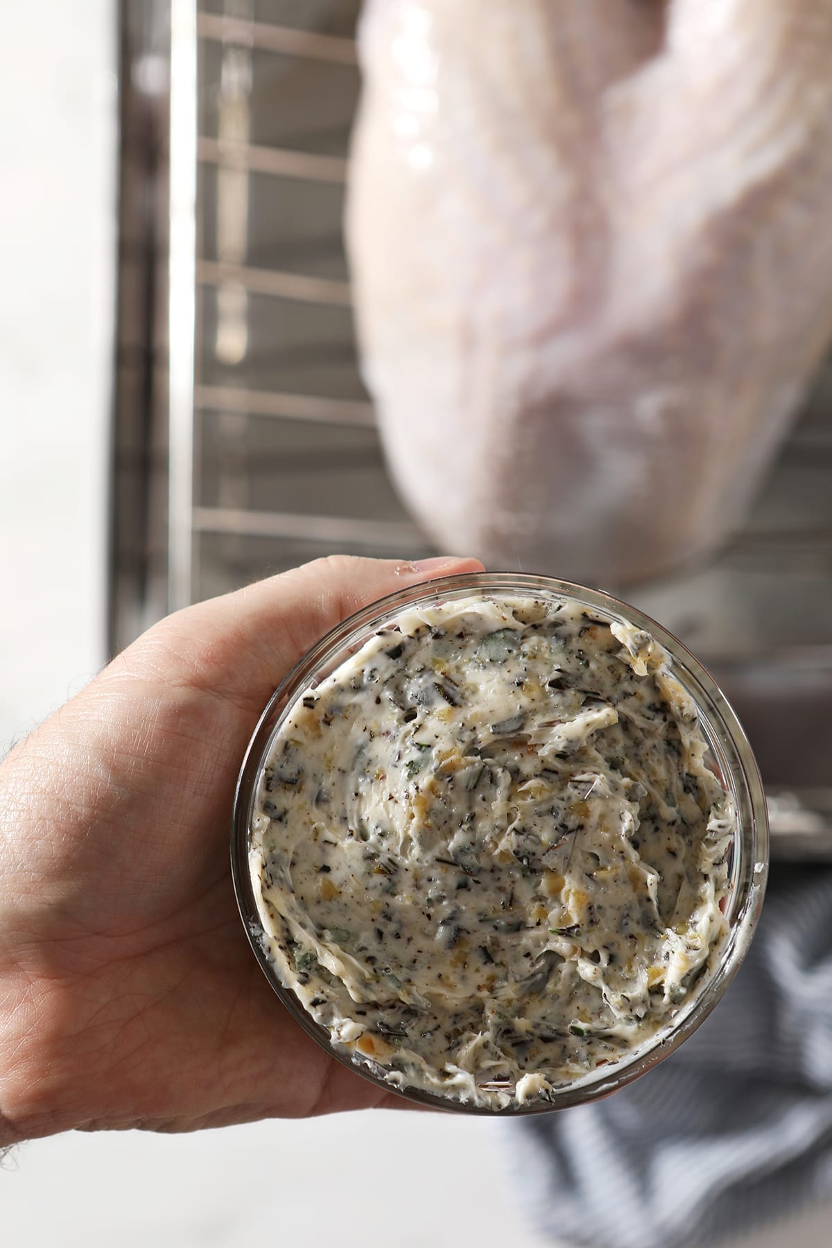 A hand holds a small glass bowl of Rosemary Garlic Herb Butter above a raw turkey breast in a roasting pan